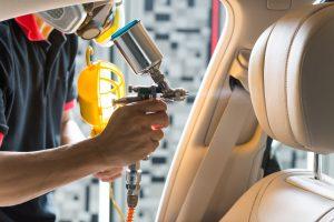 Spraying a coating on a car interior