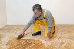man in yellow pants applying wood coating for floor
